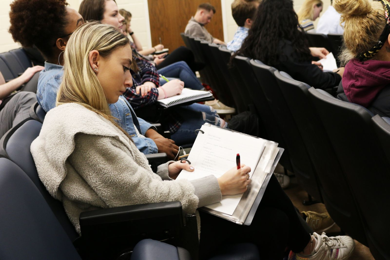 A UMD student takes notes during a lecture